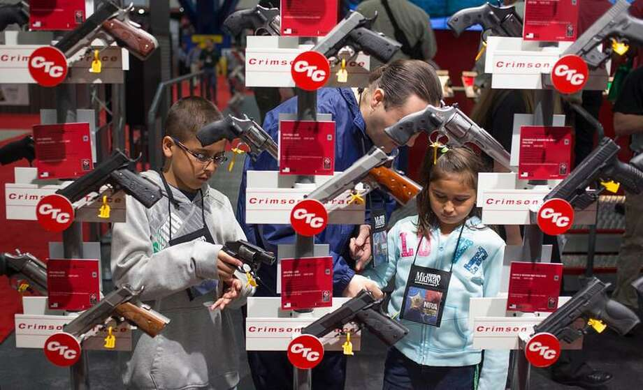 Family members look at hand guns at the George R. Brown Convention Center, the site for the National Rifle Association's annual meeting in Houston, Texas on May 4, 2013. Organizers expect some 70,000 attendees at the 142nd NRA Annual Meetings & Exhibits in Houston, which began on Friday and continues through Sunday. REUTERS/Adrees Latif Photo: REUTERS / X90022