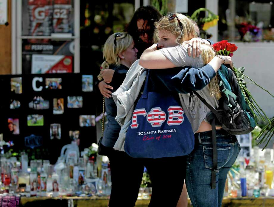 Mourners hug in front of the IV Deli Mart, where part of Friday night's mass shooting took place, on Tuesday, May 27, 2014 in the Isla Vista area near Goleta, Calif. Sheriff's officials said Elliot Rodger, 22, went on a rampage near the University of California, Santa Barbara, stabbing three people to death at his apartment before shooting and killing three more in a crime spree through a nearby neighborhood. (AP Photo/Chris Carlson) Photo: AP / AP