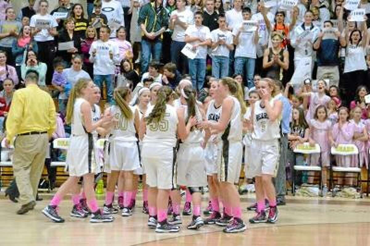 The Thomaston team congratulating Maggie Eberhardt after scoring her 1000th career point, while fans from Thomaston hold up