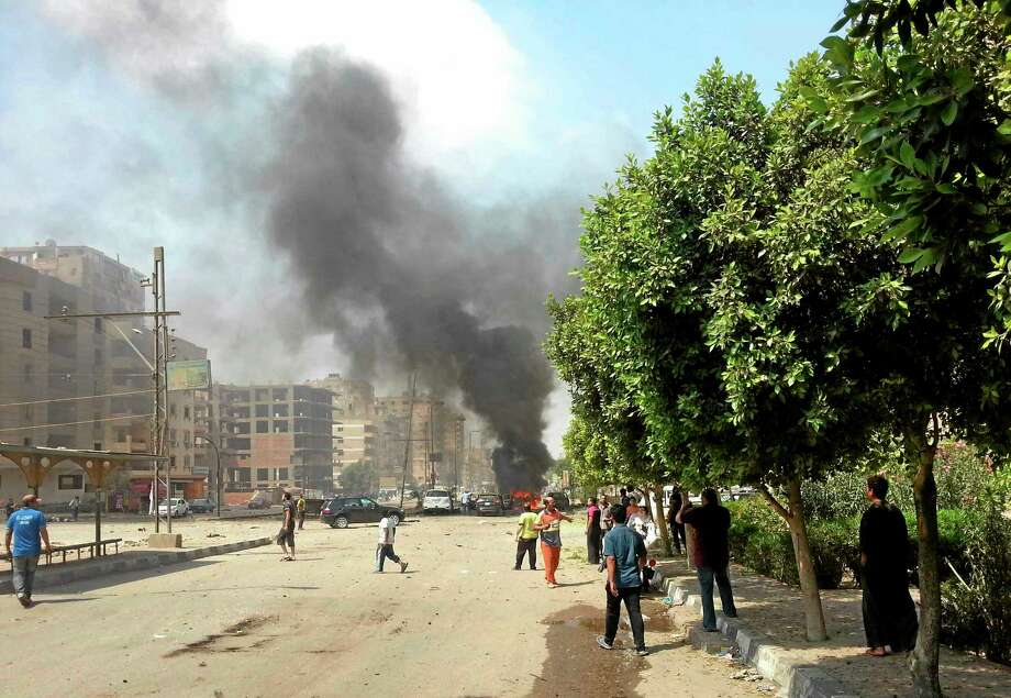 People look on as black smoke billows from burning cars moments after a bomb attack targeted the convoy of Egypt's Interior Minister Mohammed Ibrahim, in Nasr City, Egypt, Thursday. It was the first attack on a senior government official since a coup toppled the country's Islamist president July 3, 2013. (AP Photo/Ahmed Soliman) Photo: AP / AP