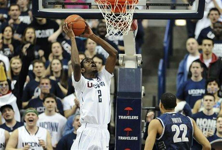 Connecticut's DeAndre Daniels lines up a dunk as Georgetown's Otto Porter Jr. (22) watches during the first half of an NCAA college basketball game in Storrs, Conn., Wednesday, Feb. 27, 2013. (AP Photo/Jessica Hill) Photo: ASSOCIATED PRESS / A2013