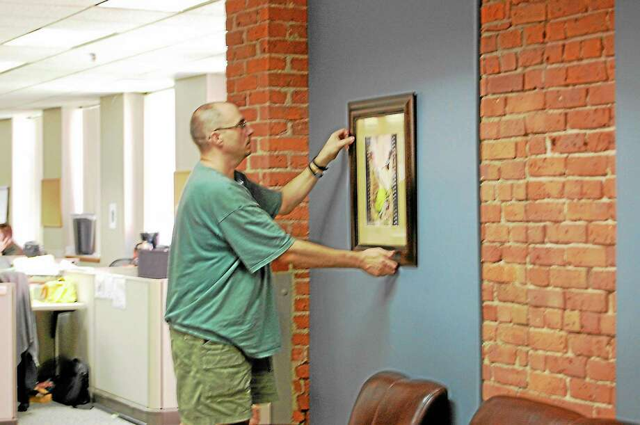 Photos by Jenny Golfin — Register Citizen Geoffrey Houghton hangs one of his paintings in the Register Citizen Newsroom. Photo: Journal Register Co.