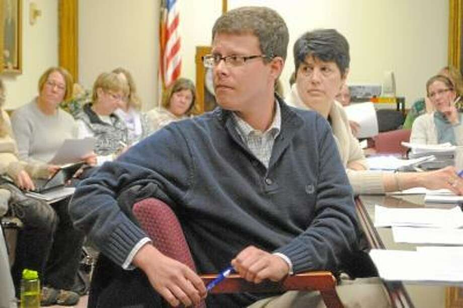 Torrington School Board Budget Committee member Christopher Rovero sits in front of schools superintendent Cheryl Klozcko and a large crowd of audience members. Jessica Glenza/Register Citizen