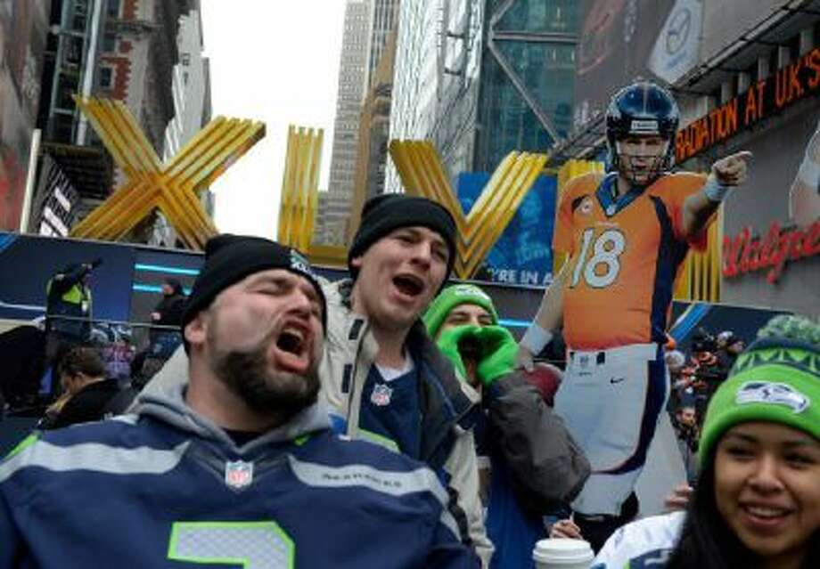 A cut out of Denver Broncos quarterback Payton Manning is hoisted over cheering Seattle Seahawks visiting Time Square in New York, NY January 31, 2014. The NFL has transformed 13 blocks of Broadway into a center for Super Bowl activity before Sundays Super Bowl.