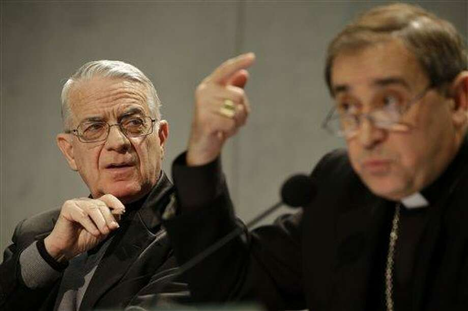 Bishop Juan Ignacio Arrieta, right, flanked by Vatican spokesman, Rev. Federico Lombardi, gestures during a press conference at the Vatican, Friday, Feb. 22, 2013. Pope Benedict XVI may enact a new law governing the upcoming conclave to elect a new pope amid continued uncertainty over when the voting can begin. Lombardi, said Wednesday that he didn't know for sure if the new law under consideration would address the timing of the conclave following Benedict's Feb. 28 resignation. (AP Photo/Gregorio Borgia) Photo: AP / AP