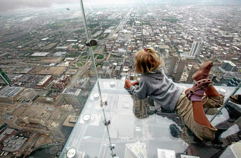 """FILE - This June 24, 2009 file photo shows Anna Kane, 5, looking down from the """"The Ledge,"""" at Chicago's Willis Tower. Officials at the building say the popular tourist attraction is safe, even though the glass ledge jutting from the building's 103rd floor appeared to crack Wednesday, May 28, 2014, beneath the feet of a visiting family. The see-through glass bays extend about four feet from the building, which was once called the Sears Tower. (AP Photo/Kiichiro Sato, File) Photo: AP / AP"""