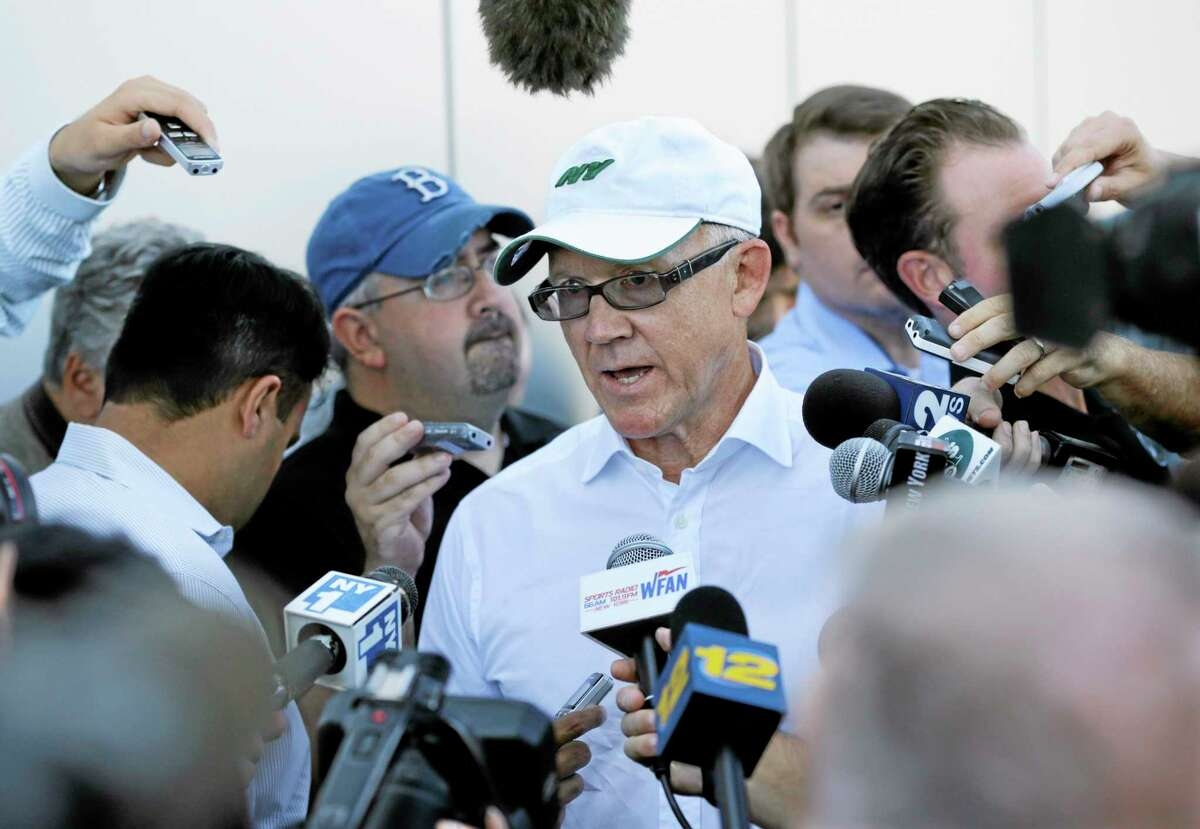 New York Jets owner Woody Johnson, center, answers a question from the media after NFL football practice in Florham Park, N.J. Wednesday, Sept. 4, 2013. (AP Photo/Mel Evans)