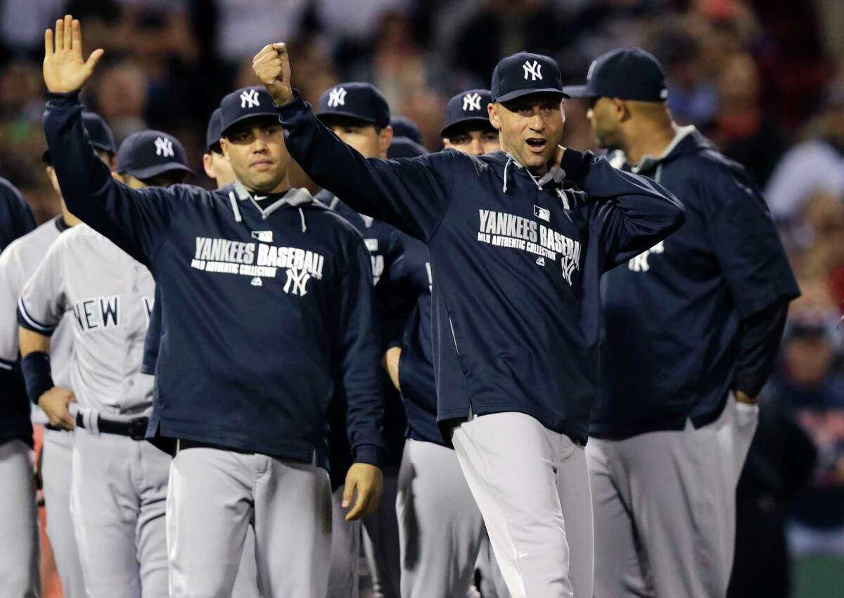 The Yankees' Derek Jeter, right, celebrates with teammates after New York defeated the Red Sox 3-2 in Friday night's game at Fenway Park in Boston.