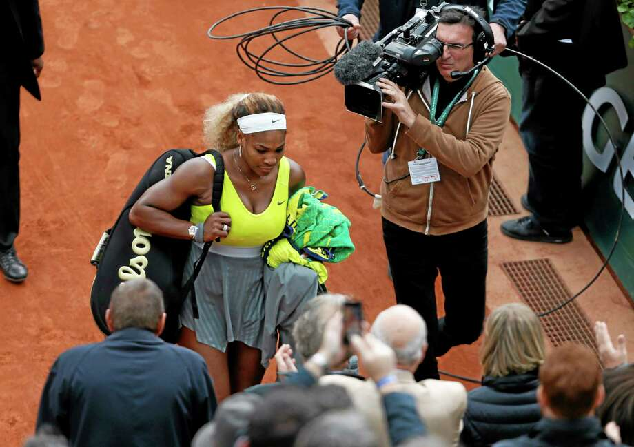 Serena Williams leaves the court after losing her second-round match 2-6, 2-6, to Garbine Muguruza at the French Open at Roland Garros stadium in Paris on Wednesday. Photo: Darko Vojinovic — The Associated Press  / AP