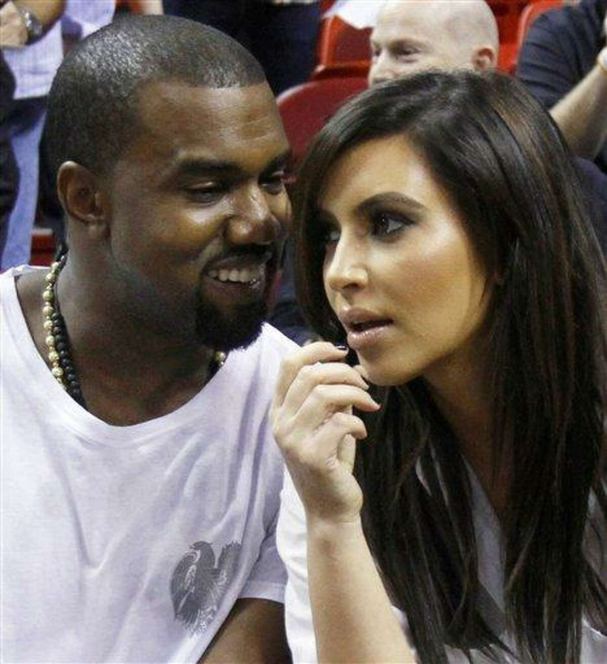 Kanye West, left, talks to his girlfriend Kim Kardashian before an NBA basketball game between the Miami Heat and the New York Knicks in Miami. Authorities say an airline employee is being investigated for allowing West and Kardashian to bypass a security checkpoint at New York's Kennedy Airport. (AP Photo/Alan Diaz, File)