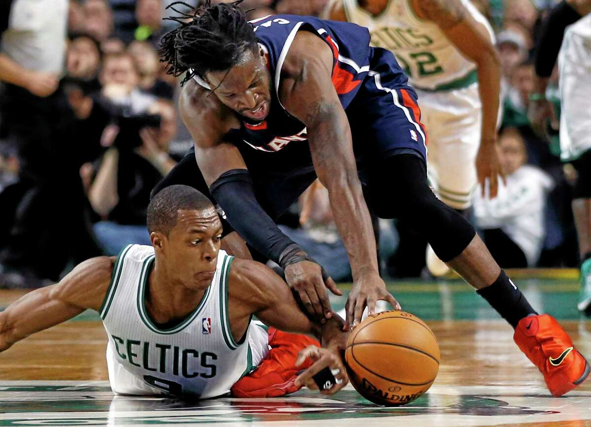 Celtics point guard Rajon Rondo dives on the floor to beat Atlanta Hawks forward DeMarre Carroll to a loose ball during a February game in Boston.
