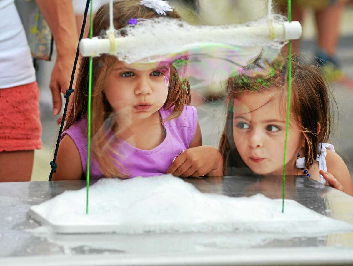 Tessa Paganini, left, of Torrington, and Piper Relihan or Litchfield, both 3, play with the bubble station set up in front of KidsPlay children's museum during Main Street Marketplace in Torrington. ° John Berry - Register Citizen.