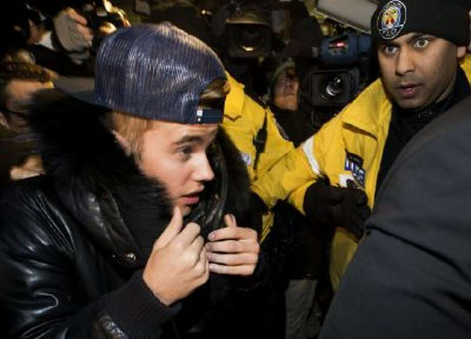 Justin Bieber is swarmed by media as he turns himself in to Toronto police Wednesday.