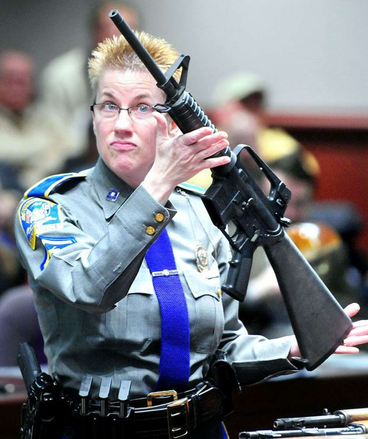 Connecticut State Police Detective Barbara Mattson holds up a Bushmaster rifle during a legislative hearing about gun control at the Legislative Office Building in Hartford on 1/28/2013.Photo by Arnold Gold/New Haven Register