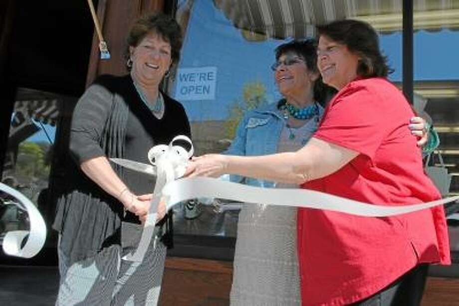 Owner of Time After Time Boutique, Pauline Maxwell, center, cuts the ribbon in front of her shop, on Winsted's Main Street. Mayor Maryanne Welcome stands to her right.
