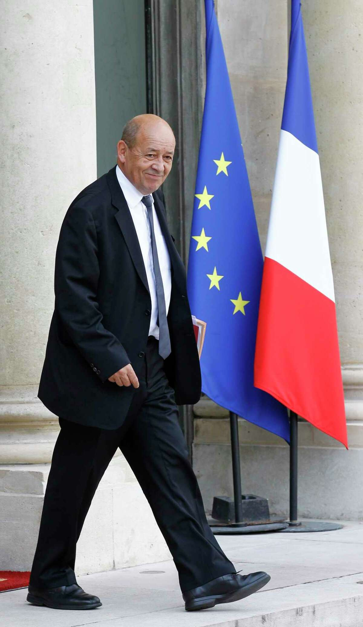 French Defense Minister Jean-Yves Le Drian leaves the Elysee Palace following a special defense meeting with French President Francois Hollande in Paris, Thursday Sept. 25, 2014. France's defense minister says the country is considering whether to extend airstrikes to Syria, and top military officials where meeting to define the country's mission against the Islamic State group. (AP Photo/Remy de la Mauviniere)