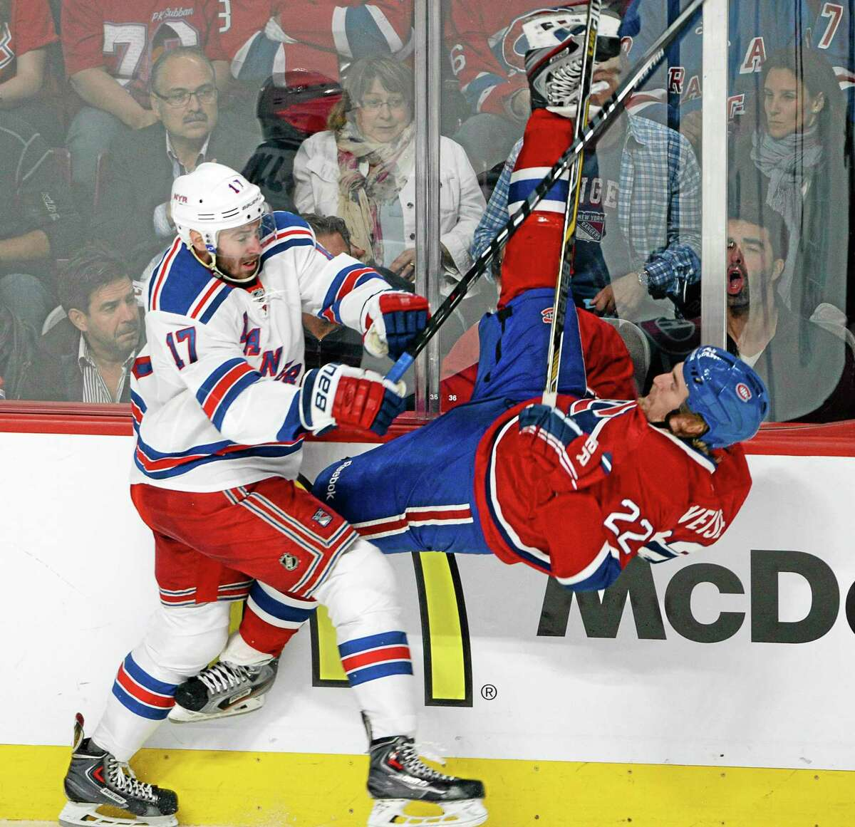 The New York Rangers' John Moore, left, takes the Canadiens' Dale Weise into the boards during the first period of Game 5 of the Eastern Conference finals on Tuesday in Montreal.