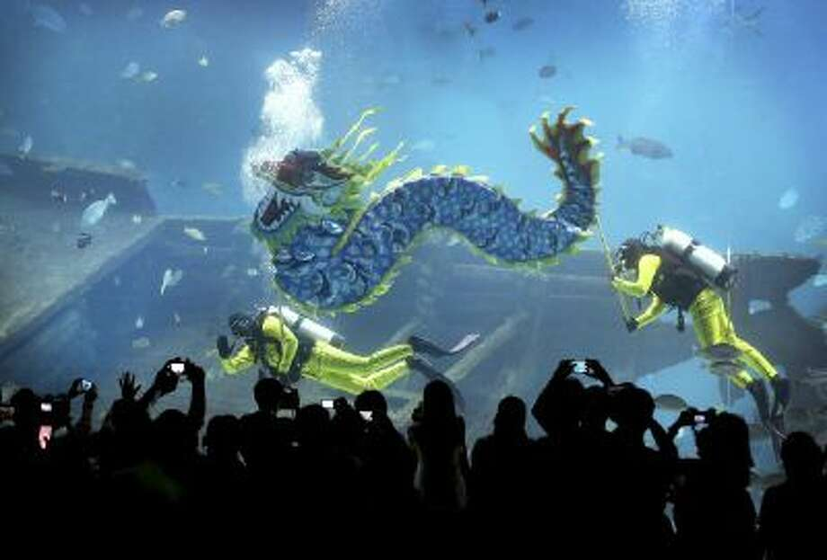 Divers carry a man-made dragon, as part of Chinese New Year dragon blessings to wish all their guests boundless energy in the Year of the Horse, Thursday, Jan. 30, 2014 at the South East Asia Aquarium at Resorts World Sentosa in Singapore. Local Chinese will celebrate the new year in the Chinese lunar calendar, which begins on Jan. 31.