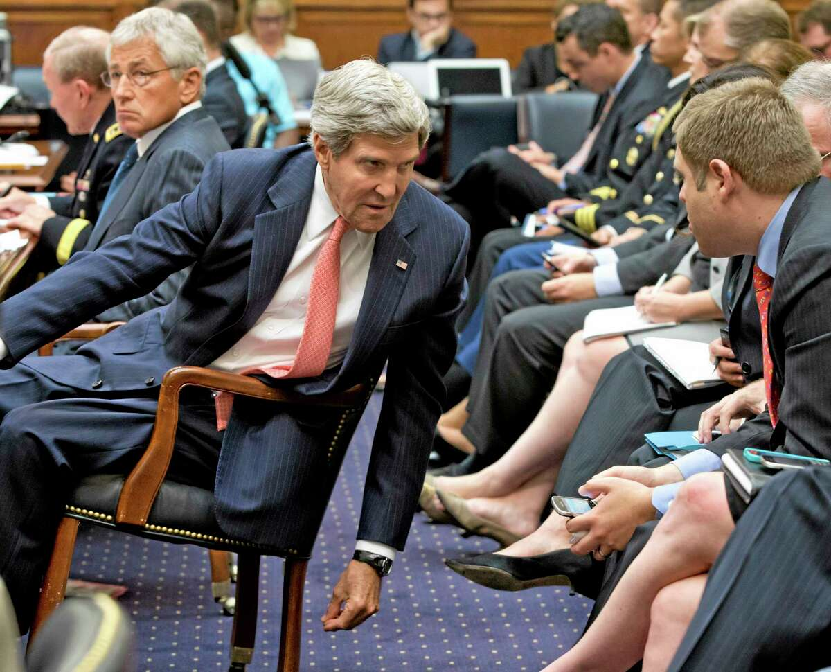 Secretary of State John Kerry leans over to confer with his advisers, on Capitol Hill in Washington, Wednesday, Sept. 4, 2013, as he testified before the House Foreign Affairs Committee to advance President Barack Obama's request for congressional authorization for military intervention in Syria, a response to last month's alleged sarin gas attack in the Syrian civil war. Defense Secretary Chuck Hagel is at left. (AP Photo/J. Scott Applewhite)