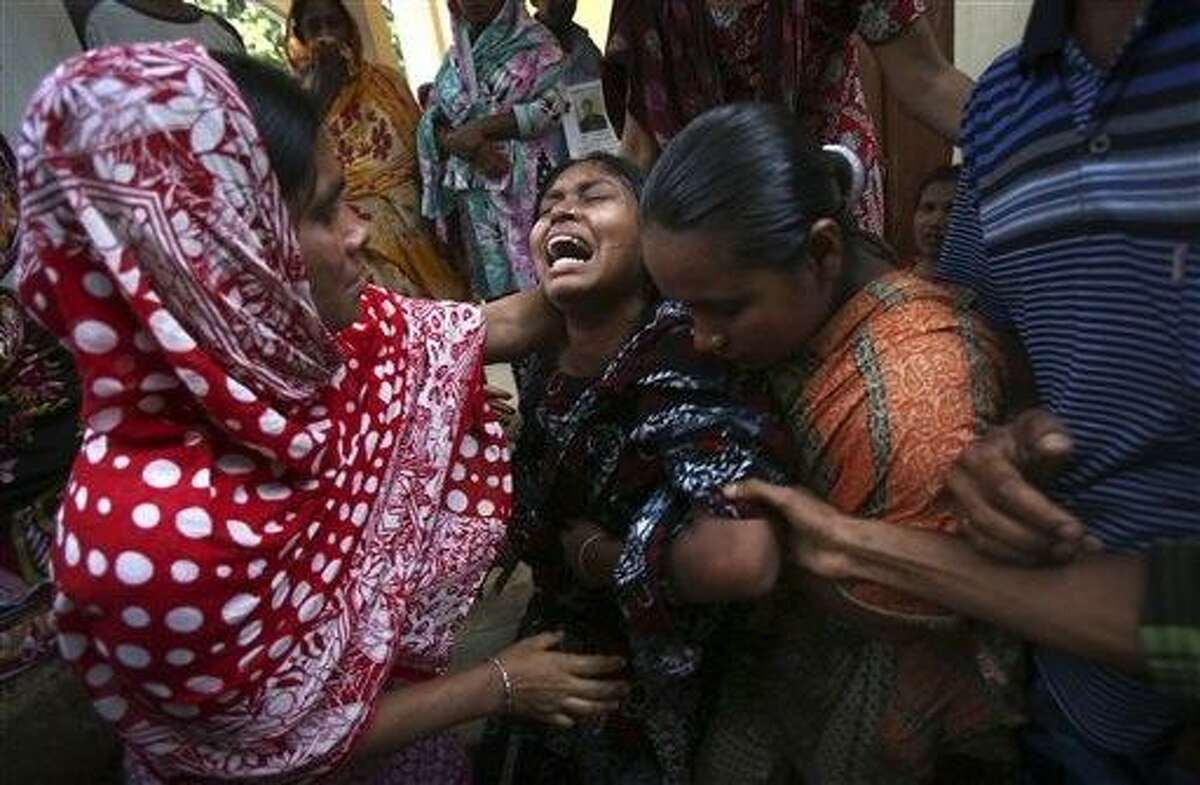 A woman is comforted by family members and others after she identified the body of her relative recovered from the rubble of the garment factory building which collapsed last week, in Savar, near Dhaka, Bangladesh, Friday, May 3, 2013. Authorities suspended the mayor of the suburb of Savar, where the building was located, and arrested an engineer who called for the building's evacuation last week but was also accused of helping the owner add three illegal floors to the eight-story structure. (AP Photo/Wong Maye-E)