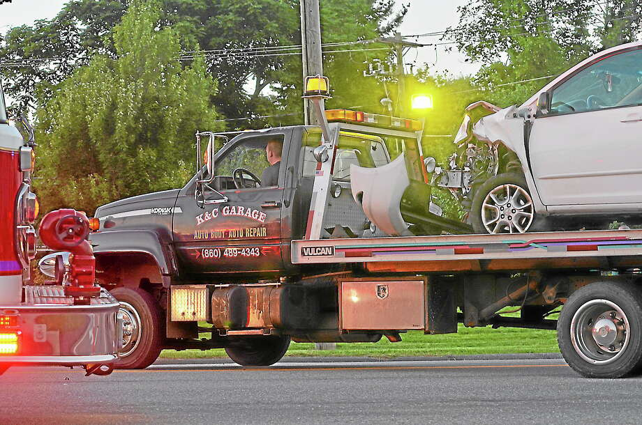 A damaged vehicle is loaded onto a tow truck on East Main Street near the intersection with Kennedy Drive around 7 p.m. following a multi-car accident Wednesday evening. Photo: Photo By Tom Caprood—Register Citizen