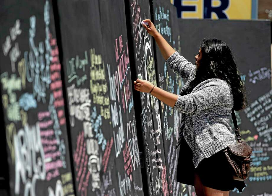Daniela Bayon writes on a remembrance wall across the street from the IV Deli Mart, where part of the mass killings took place, on Tuesday, May 27, 2014 in the Isla Vista area near Goleta, Calif. Sheriff's officials said Elliot Rodger, 22, went on a rampage near the University of California, Santa Barbara, stabbing three people to death at his apartment before shooting and killing three more in a crime spree through a nearby neighborhood. (AP Photo/Chris Carlson) Photo: AP / AP