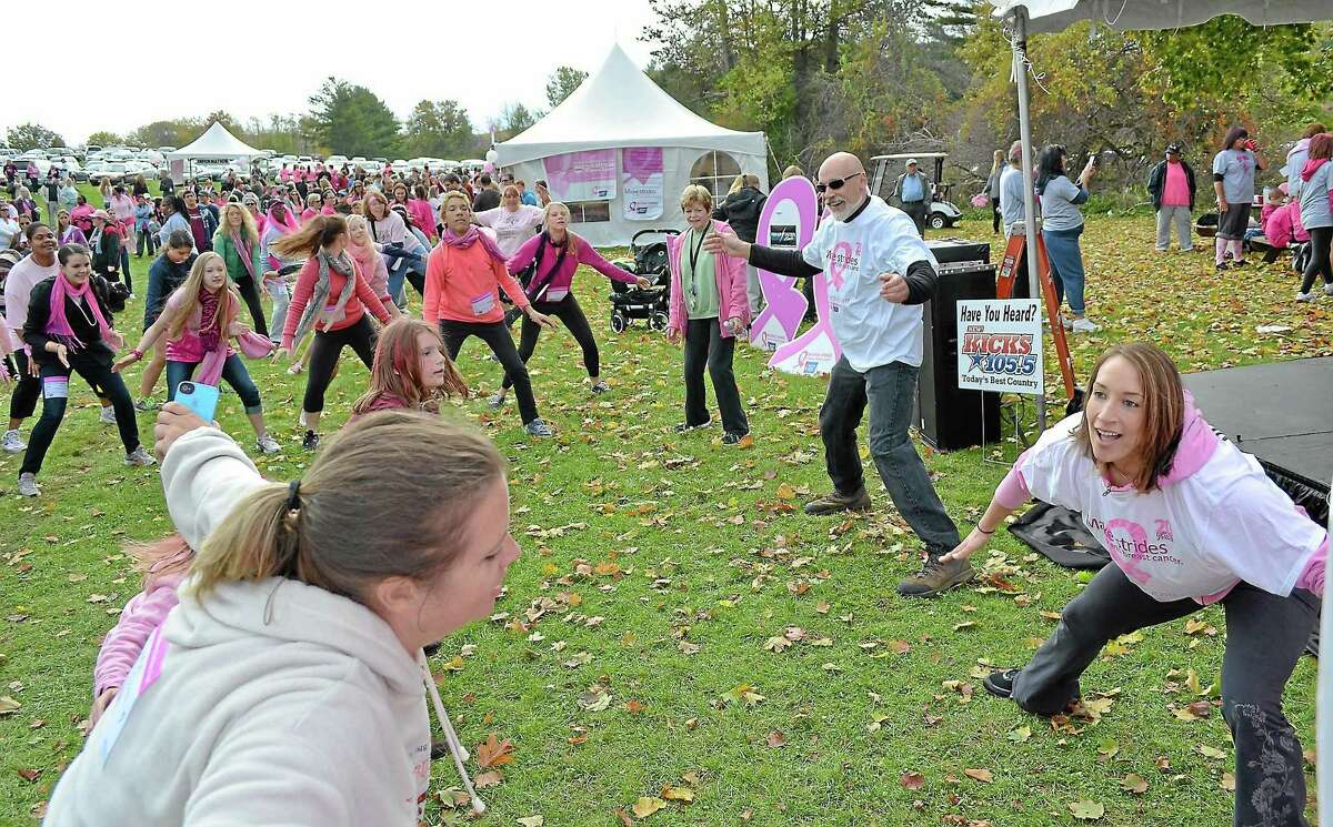 Renee Rossi, right, and Peter Bergamo of Litchfield Athletic Club helps get the crowd warmed up before Sunday's Making Strides Against Breast Cancer walk at the White Memorial Conservation Center in Litchfield.