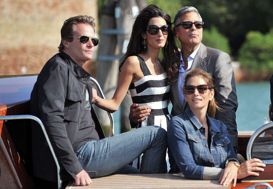 George Clooney, top right, his fiancee Amal Alamuddin, Cindy Crawford, bottom right and her husband Rande Gerber arrive in Venice, Italy, Friday, Sept. 26, 2014. George Clooney and his fiancee Amal Alamuddin arrived in Venice on Friday for their weekend wedding extravaganza, accompanied by loved ones and trailed by a clutch of photographers who recorded their passage along the picturesque Grand Canal. (AP Photo/Luigi Costantini) Photo: AP / AP