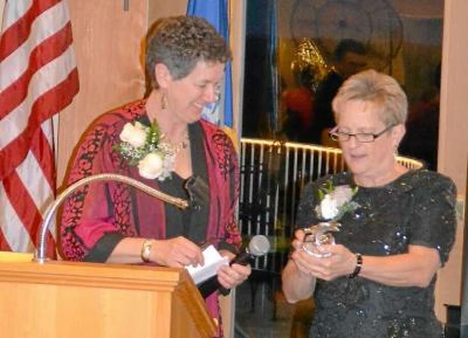 Kate Hartman/Register Citizen -- Barbara Spiegel, executive director of the Susan B. Anthony Project, left, accepts an on behalf of her staff from Gail Olsen during the United Way of Northwest Connecticut's inaugural Women's Initiative Gala.