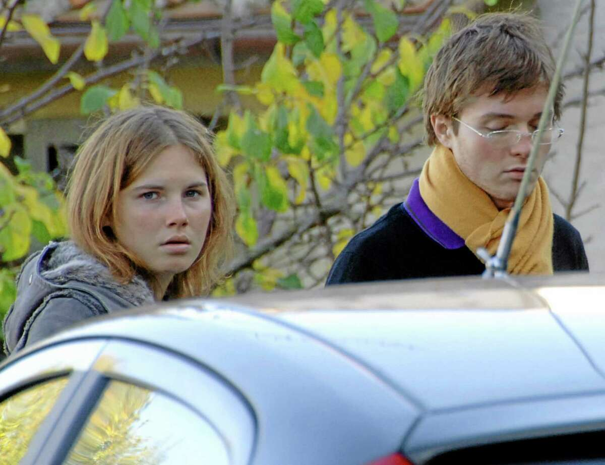 FILE - In this Friday Nov. 2, 2007 file photo Amanda Knox, left, and Raffaele Sollecito, stand outside the rented house where 21-year-old British student Meredith Kercher was found dead Friday, in Perugia, Italy. An appeals court in Florence has upheld the guilty verdict against U.S. student Amanda Knox and her ex-boyfriend for the 2007 murder of her British roommate. Knox was sentenced to 28 1/2 years in prison, raising the specter of a long legal battle over her extradition. After nearly 12 hours of deliberations Thursday, Jan. 30, 2014 the court reinstated the guilty verdict first handed down against Knox and Raffaele Sollecito in 2009. (AP Photo/Stefano Medici)