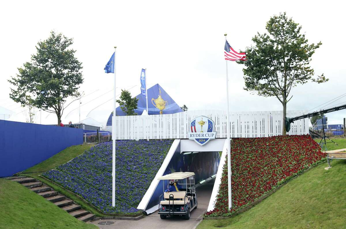 A golf buggy drives through a walkway decorated with former winning captains and players of the Ryder Cup Thursday at Gleneagles, Scotland.