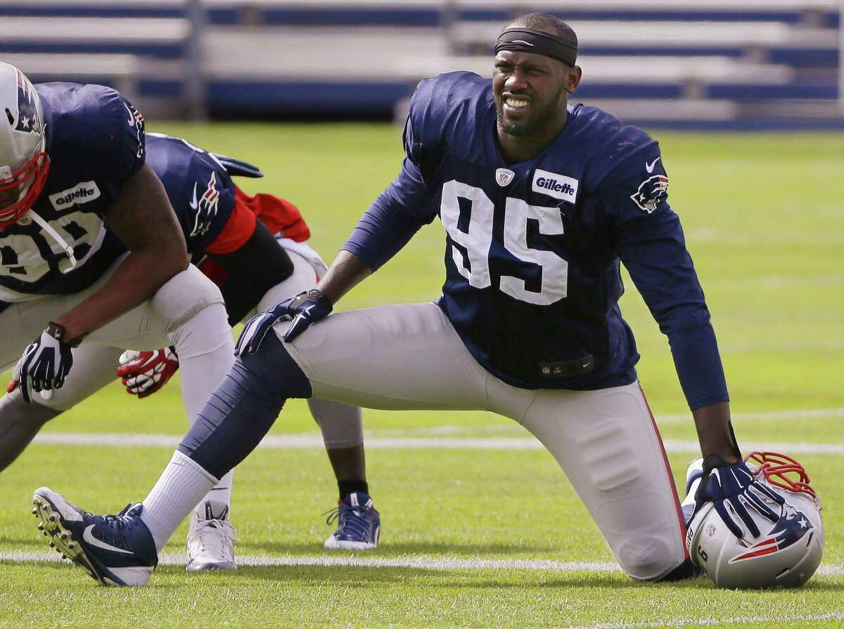 New England Patriots defensive end Chandler Jones (95) stretches before practice Wednesday at the team's facility in Foxborough, Mass.