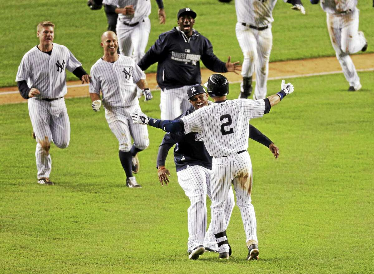 Derek Jeter (2) celebrates with teammates after driving in the winning run against the Orioles Thursday in his final game at Yankee Stadium.