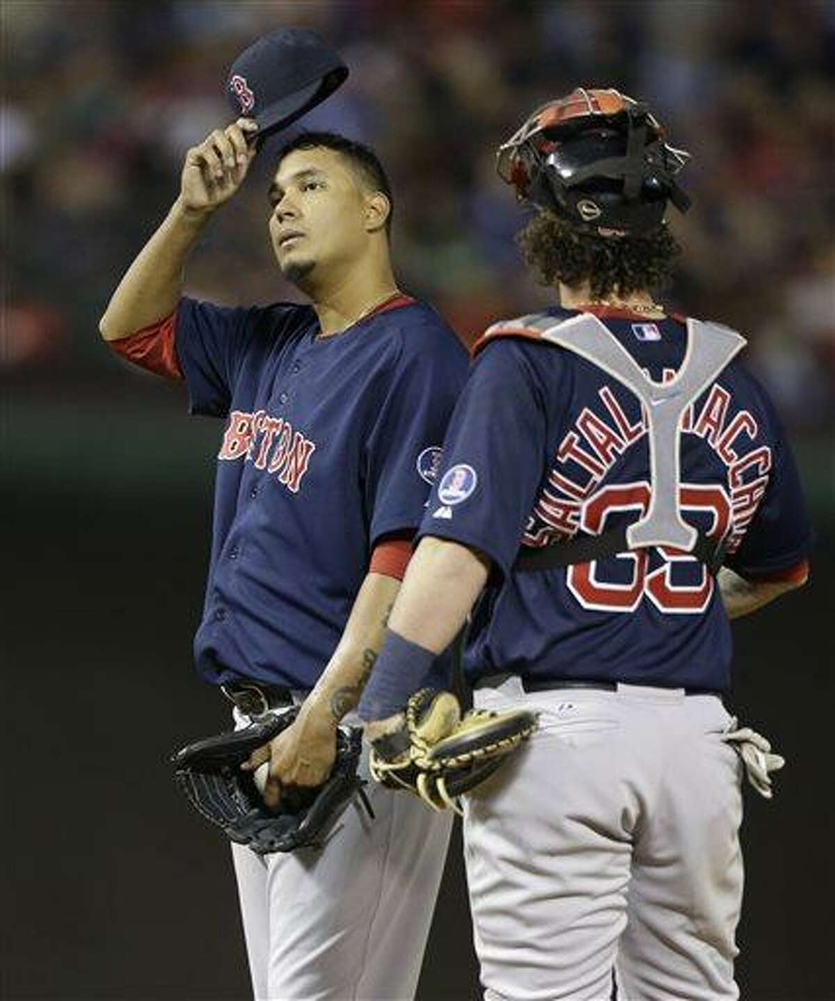 Boston Red Sox starting pitcher Felix Doubront, left, takes off his cap and looks up next to catcher Jarrod Saltalamacchia after giving up five runs to the Texas Rangers during the fourth inning of a baseball game Friday, May 3, 2013, in Arlington, Texas. (AP Photo/LM Otero)