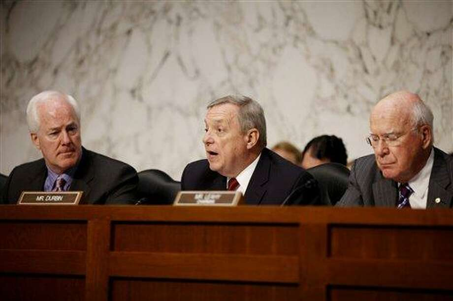 Sen. Richard Durbin, D-Ill., center, flanked by Sen. John Cornyn, R-Texas, left, and Sen. Patrick Leahy, D-Vt., speaks during a meeting on Capitol Hill in Washington. The Senate holds its second hearing Tuesday, Feb. 12, 2013, on gun curbs since the December 2012 shooting deaths of 20 first-graders in Newtown, Conn. This time, a Senate Judiciary subcommittee is examining the constitutionality and effectiveness of federal firearms limits. ?We need to keep guns out of the hands of criminals and those who are mentally unstable,? Durbin, D-Ill., said in a brief interview Monday, Feb. 11, 2013. ?I hope everyone will acknowledge what within our Constitution is not only an individual right to bear arms, but the collective right of Americans to be safe.? (AP Photo/Charles Dharapak, File) Photo: AP / AP