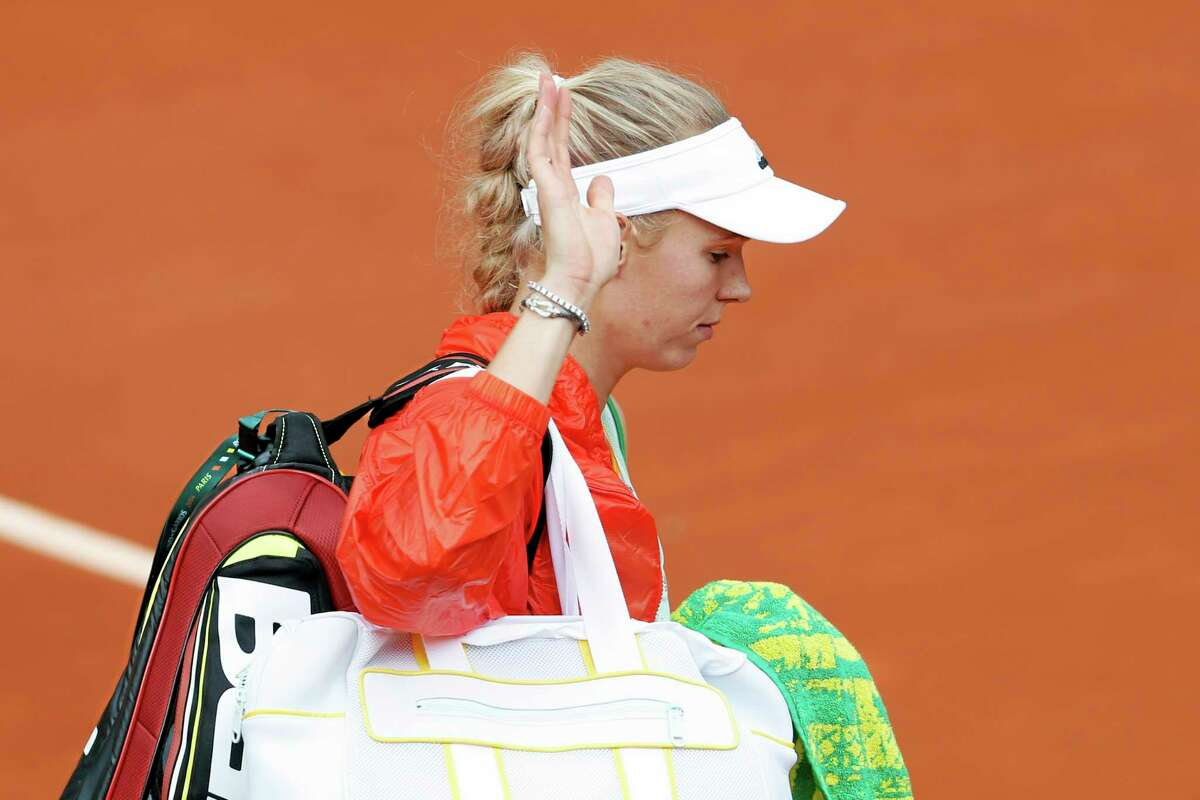 Denmark's Caroline Wozniacki waves goodbye after losing the first round match of the French Open tennis tournament against -Belgium's Yanina Wickmayer at the Roland Garros stadium, in Paris, France, Tuesday, May 27, 2014. (AP Photo/Darko Vojinovic)