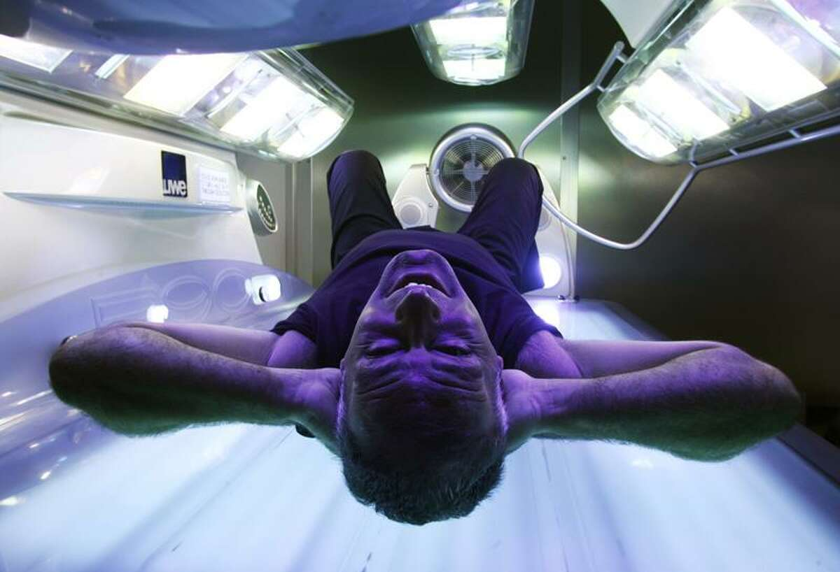 Former Scottish politician Tommy Sheridan poses on a sunbed in a tanning salon. (Reuters/David Moir)