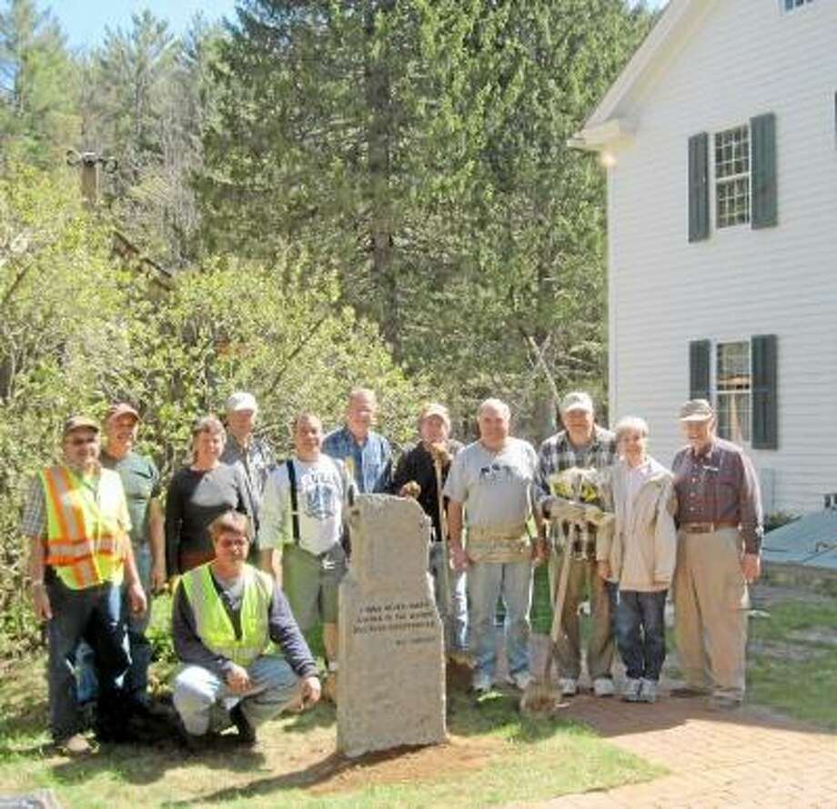 "Members of the Barkhamsted Historical Society add a hitching post on the grounds of Squire's Tavern in Barkhamsted on Wednesday, May 1, 2013. The 700-pound hitching post bears a quote from Walt Landgraf: ""I have never taken a walk in the woods and been disappointed."" Landgraf was a former president of the society who was instrumental in helping get state funding to restore the grounds and build a barn which will be dedicated to him on Saturday. (SUBMITTED PHOTO/PAUL HART)"