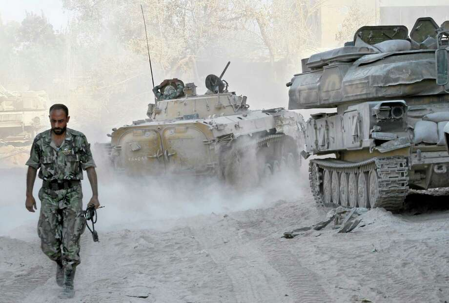 FILE - In this Saturday, Aug. 24, 2013 file photo taken on a government organized media tour, a Syrian army soldier walks on a street in the Jobar neighborhood of Damascus, Syria. As the Obama administration tries to prod Congress into backing armed action against Syria, the regime in Damascus is hiding military hardware and shifting troops out of bases into civilian areas. (AP Photo, File) Photo: AP / AP