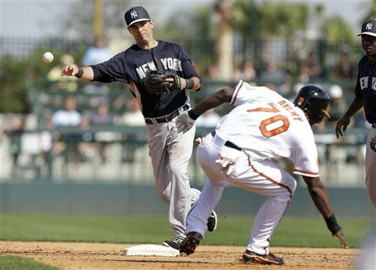 New York Yankees shortstop Gil Velazquez throws to first base after forcing out Baltimore Orioles' Xavier Avery at second base during the fifth inning of a baseball spring training exhibition game, Monday, Feb. 25, 2013, in Sarasota, Fla. (AP Photo/Charlie Neibergall)