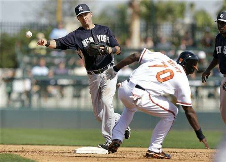 New York Yankees shortstop Gil Velazquez throws to first base after forcing out Baltimore Orioles' Xavier Avery at second base during the fifth inning of a baseball spring training exhibition game, Monday, Feb. 25, 2013, in Sarasota, Fla. (AP Photo/Charlie Neibergall) Photo: ASSOCIATED PRESS / AP2013