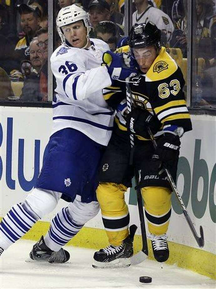 Toronto Maple Leafs defenseman Carl Gunnarsson (36) and Boston Bruins left wing Brad Marchand (63) grapple along the boards for the puck during the second period in Game 1 of a first-round NHL hockey playoff series in Boston, Wednesday, May 1, 2013. (AP Photo/Elise Amendola) Photo: AP / AP