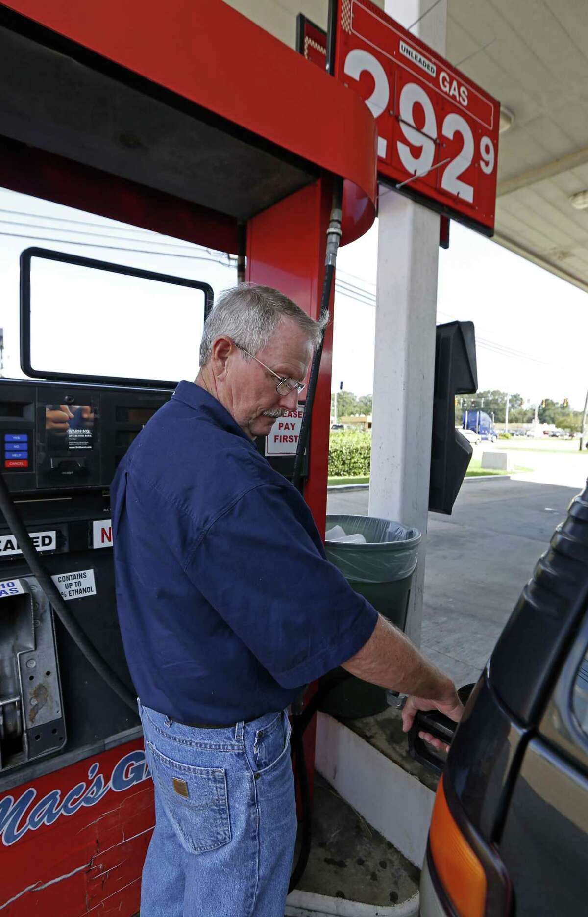 """In this Wednesday, Sept. 24, 2014 photo, Foster Gilley, of Chatom, Ala., fills his SUV's tank with $2.92-per-gallon regular gas at Mac's Gas in Richland, Miss. The typical autumn decline in gasoline prices is getting a big push lower by falling global oil prices. By the end of the year, up to 30 states could have an average gasoline price of under $3 a gallon. Gilley and his wife were visiting his brother in Vicksburg and were """"enjoying the lower prices,"""" he said."""