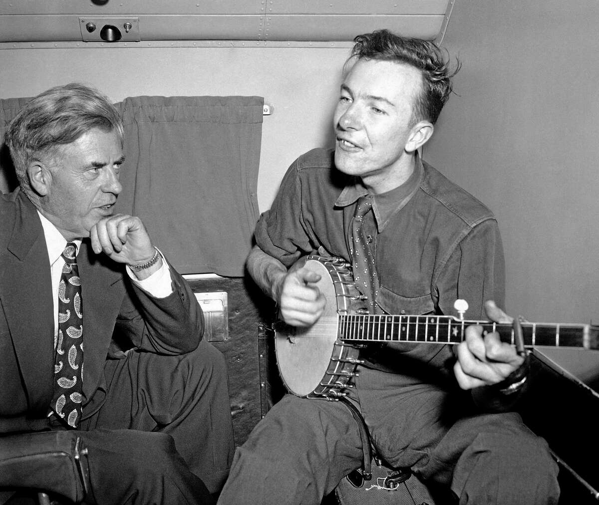 FILE - In this Aug. 28, 1948 file photo, Henry A. Wallace, a Progressive Party presidential candidate, listens to Pete Seeger on a plane between Norfolk and Richmond, Va. (AP Photo/File)