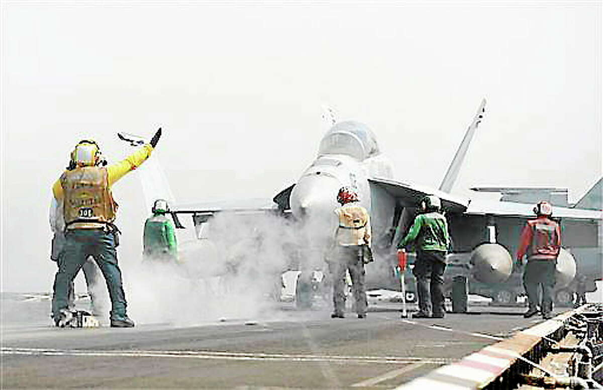 In this photo provided by the U.S. Navy, an F/A-18F Super Hornet assigned to the Black Knights of Strike Fighter Squadron (VFA) 154 prepares to launch from the flight deck of the aircraft carrier USS Nimitz in the Red Sea on Tuesday, Sept. 3, 2013. The USS Truman arrived in the region to take the place of the USS Nimitz, which was supposed to head home. But the Navy ordered the Nimitz to stay for now. U.S. officials, however, have described the decision as prudent planning and have said it doesn't suggest the Nimitz would play a role in any possible strikes in Syria. (AP Photo/U.S. Navy, MC3 Nathan R. McDonald, Released)