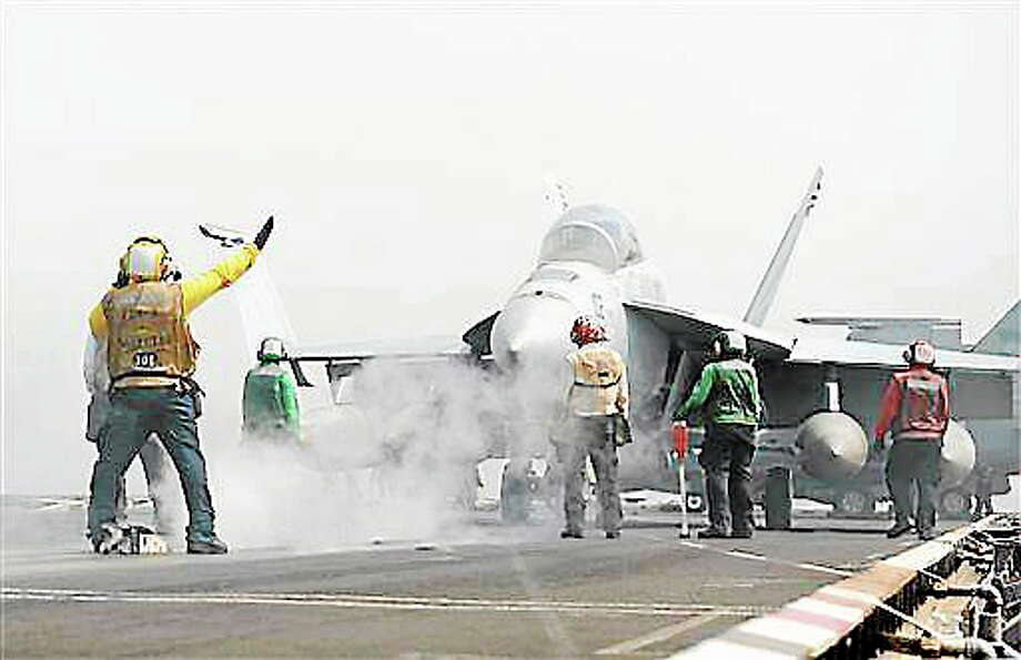 In this photo provided by the U.S. Navy, an F/A-18F Super Hornet assigned to the Black Knights of Strike Fighter Squadron (VFA) 154 prepares to launch from the flight deck of the aircraft carrier USS Nimitz in the Red Sea on Tuesday, Sept. 3, 2013.   The USS Truman arrived in the region to take the place of the USS Nimitz, which was supposed to head home. But the Navy ordered the Nimitz to stay for now. U.S. officials, however, have described the decision as prudent planning and have said it doesn't suggest the Nimitz would play a role in any possible strikes in Syria.  (AP Photo/U.S. Navy, MC3 Nathan R. McDonald, Released) Photo: AP / US Navy
