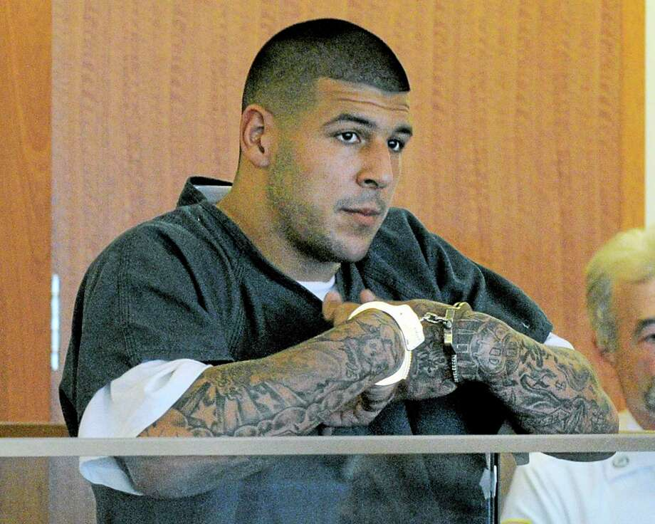 FILE - In this June 27, 2013 file photo, former New England Patriots football standout Aaron Hernandez stands during a bail hearing in Superior Court in Fall River, Mass., charged with killing Odin Lloyd. Hernandez is scheduled to be arraigned May 28, 2014, on two unrelated murder charges in the 2012 shooting deaths of Daniel de Abreu and Safiro Furtado in Boston. Prosecutors are also seeking assistance from tattoo artists who may have inked Hernandez's right arm between February 2012 and June 2013. The tattoo artists are considered witnesses, not suspects. (AP Photo/Boston Herald, Ted Fitzgerald, Pool, File) Photo: AP / Pool, Boston Herald