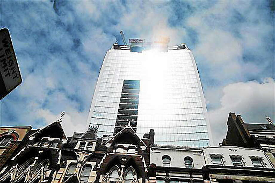 The 37-storey skyscraper at 20 Fenchurch Street, which is still under construction in the City of London, Tuesday, Sept. 3, 2013.  Developers for an unfinished skyscraper in central London say they are investigating the way the building reflects bright sunlight _ after claims that the intense glare melted parts of a car parked nearby. The companies behind the skyscraper, nicknamed the ?Walkie-Talkie? because of its curved shape, are responding to complaints from the owner of a Jaguar who told the BBC that the mirror, panels and the Jaguar badge had all melted from the concentrated heat of sunlight reflected from the building. (AP Photo/PA, Andy Scofield)  UNITED KINGDOM OUT  NO SALES  NO ARCHIVE Photo: AP / PA
