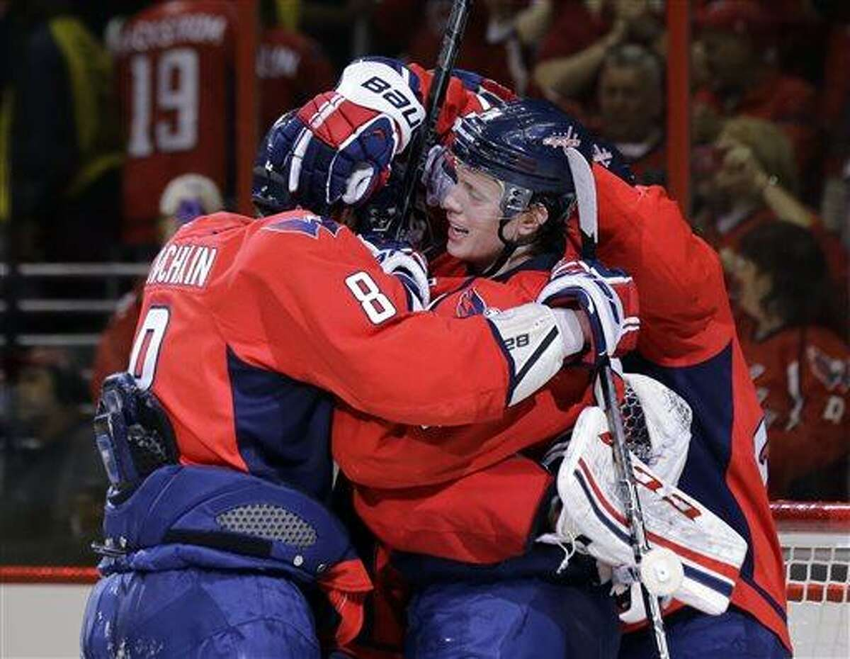 Washington Capitals left wing Alex Ovechkin (8), from Russia, and defenseman John Carlson (74) and others celebrate after Game 1 of a Stanley Cup NHL playoff hockey series against the New York Rangers, Thursday, May 2, 2013, in Washington. The Capitals won 3-1. (AP Photo/Alex Brandon)