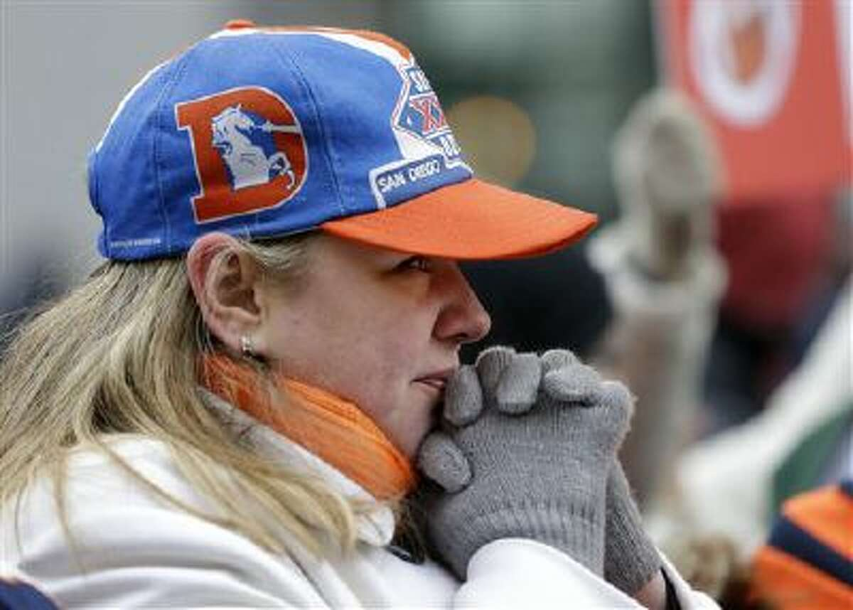 Denver Broncos fan Nancy Scollon tries to keep warm as she waits for the Broncos players to arrive at their team hotel Sunday in Jersey City, N.J.